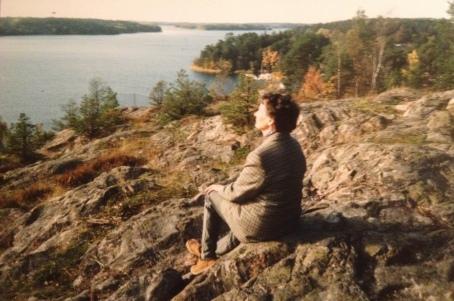 Svea sitter på en klippa och tittar ut över fjärden
